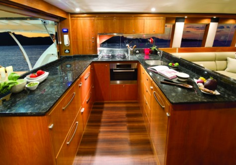 The aft galley with awning window is perfect for alfresco dinning in the cockpit Shown here in high gloss cherry cabinetry