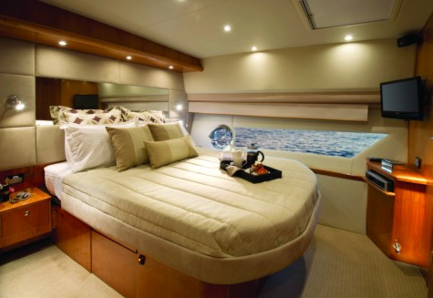 The master stateroom with hull window is luxuriously appointed with plenty of storage for extended voyages. Shown here in high gloss cherry cabinetry